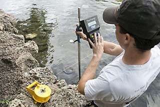 Brian Hunt of the Barton Springs/Edwards Aquifer Conservation District measures spring flow just below Barton Springs Pool.