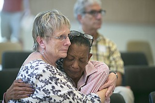 Carol Cook (l) and Rosemary Lester, family members of SSLC residents, embrace each other for support.