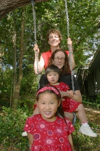 Suzanne Bryant (top) and her partner Sarah Goodfriend with children Ting Lan and Dawn