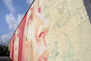 A faint outline of the <i> L&oacute;teria </i>mural can be seen through the new mural.