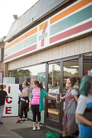 Students line up outside a 7-Eleven to promote healthy eating.