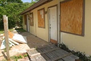 A boarded-up apartment building on Sam Rayburn Drive is surrounded by trash and discarded building supplies.