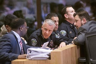 Assistant City Managers Mark Washington and Rey Arellano (hidden) talk with Police Chief Brian Manley during Wednesday's specially called City Council meeting.