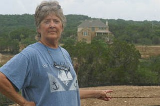 Lick Creek resident Pepper Morris serves as a volunteer water quality monitor for the LCRA and notified the agency that the creek was showing evidence of degradation. Behind her is the model home for West Cypress Hills.
