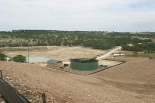 Sewage plant at the foot of West Cypress Hills development under construction, with detention pond at left and dam just beyond it