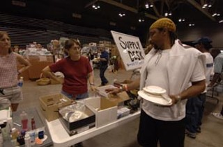 A Katrina evacuee scans tables for needed living supplies as 