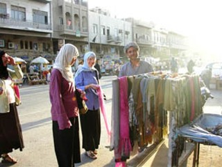 Female members of the Christian Peacemaker Teams shopping at the street vendors in Karrada, Iraq. They are wearing now-typical Iraqi women's garb, so as not to stand 