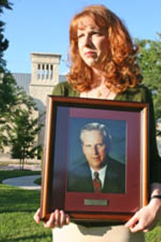 Lari Burson holding a portrait of her late father, Mike Burson