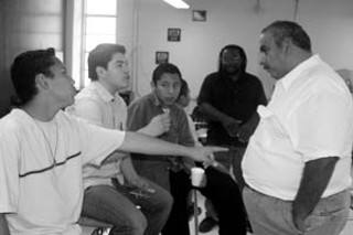 Eduardo Sifuentes, Luis Miguel Orozco, and German Sifuentes discuss politics with Alfredo Santos. Tim Eubanks of Austin Voices for Education and Youth stands in the background.