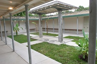 Restored men's changing area, showing the open roof, shaded wall benches, and central showering area, and landscaping.