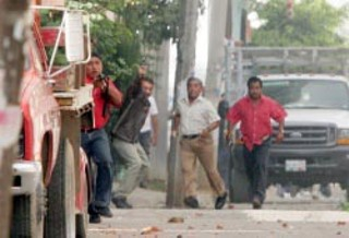 This photo from the Mexican newspaper <i><b>El Universal</b></i>, taken just as Brad Will was killed, shows identifiable Oaxaca police officers firing at the crowd. From left to right, Juan Carlos Soriano, aka El Chapul&iacute;n; Comandant Manuel Aguilar; Pedro Carmona; and Abel Santiago, aka El Chino.
