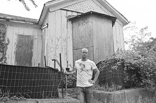 Darien Ligarde stands in front of a dilapidated ARA home on Olive Street that he and his wife, Stephanie Villard, had expected to be living in by now.