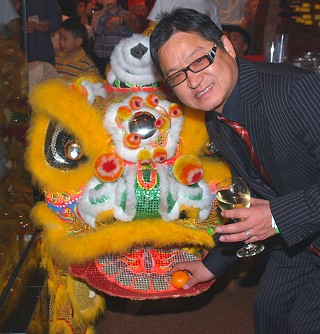 Chinatown restaurant owner Ronald Cheng celebrates the lunar new year by feeding the dragon a tangerine.