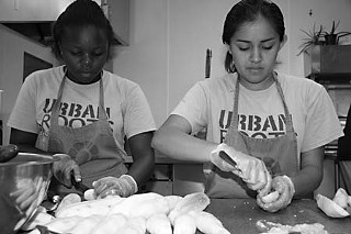 Kayla Washington and Veronica Garcia cutting cucumbers at Caritas