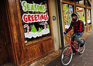 A bicyclist keeps warm as she rides down Sixth Street, past Buffalo Billiards.