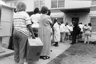 Residents wait in line at the weekly Capital Area Food Bank food drop.