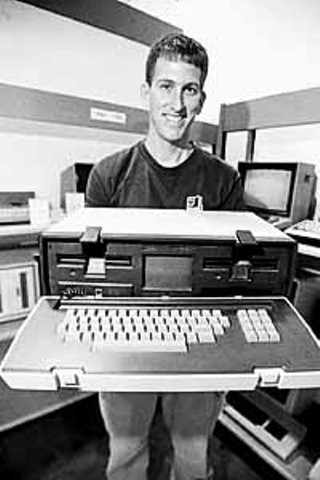 Alex Bilstein holding the first luggable computer, the 1981 Osborne 1