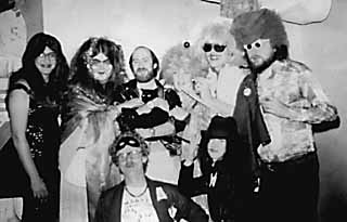 Mardi Gras '77 backstage at Armadillo World Headquarters after the Fools show. Top row  (l-r): host and emcee Micael Priest; Big Rikke, the irrepressible Guacamole Queen; Van Wilks, Guitar God and leader of the Fools; Spook, the Armadillo Rock & Roll Cat; Margaret and Stephen Moser, the Nurses From Outer Space; Big Boy Medlin, sports editor for the <i>Austin Sun</i> and founder of E! the Entertainment Network. Bottom Row (l-r): Marty  Manning, KOKE-FM  morning man and TV bingo host; Janet Burris, Sheauxnough Studios business manager.
