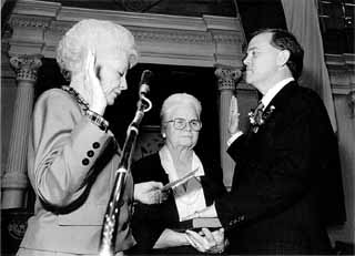 Glen Maxey is sworn into office in 1991 by then-Gov. Ann Richards. Holding the Bible is Maxey's mother, Mary. For more on Maxey, see Capitol Chronicle.