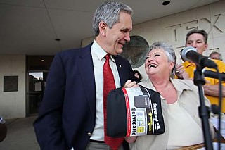 "Texas AFL-CIO President Becky Moeller provides U.S. Rep. Lloyd Doggett, D-Austin, a ""survival kit"" to help him on his return to Congress to fight for health care reform. Also saluting Doggett at the Labor Day fish fry were the Austin Central Labor Council and the Texas and national Alliance for Retired Americans. Doggett said he would fight for a ""strong public option"" in the reform legislation and against attacks by ""know-nothing, fear-mongering wing nuts – about the only people left in the Republican Party."""