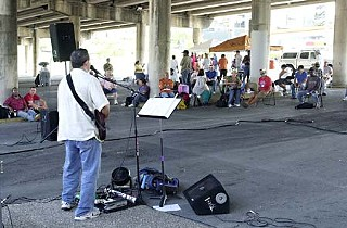 Homeless men and women attend church  under the I-35 bridge.