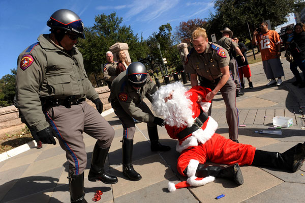 Occupy Austin participant, James Peterson dressed as Santa Claus, is arrested by DPS troopers after he handed out chalk to children after an event at the Texas Capitol. Peterson wrote with chalk himself and encouraged the children to consider writing Christmas wishes such as
