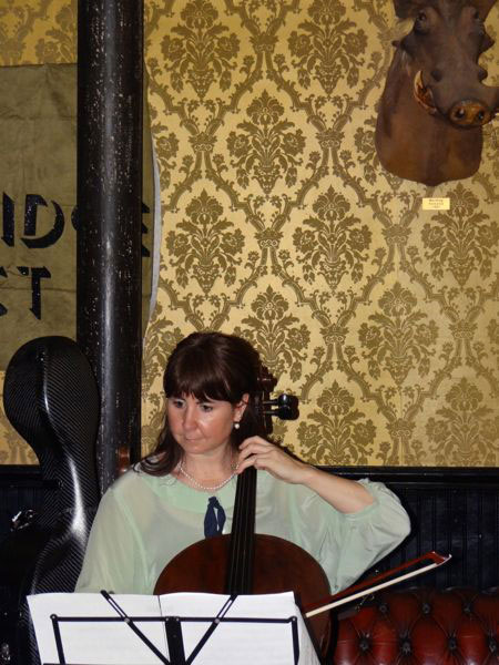 Cellist Karla Hamelin thrums under the watchful snout of the Volstead boar