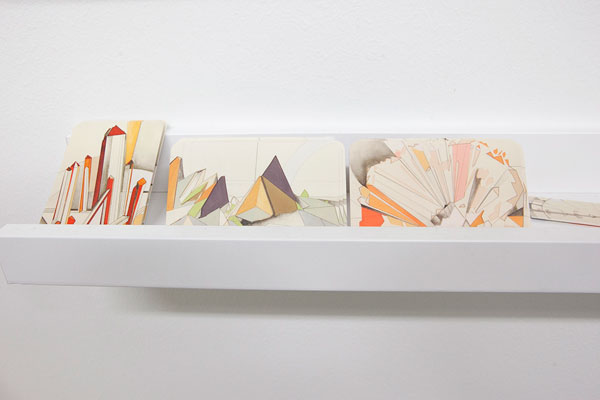 Drawings referencing the structure of minerals are leaned out on a shallow shelf