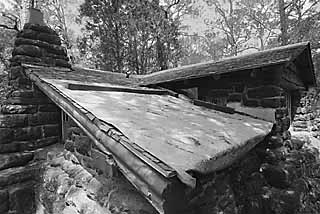 A tarp covers the roof of this Bastrop State Park cabin in need of repair.